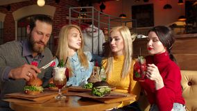 A group of young and cheerful friends eat delicious burgers in a trendy cafe. Teenagers enjoy eating hamburgers in the cafe, slow motion stock video footage