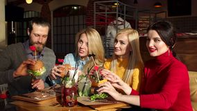 A group of young and cheerful friends eat delicious burgers in a trendy cafe. Teenagers enjoy eating hamburgers in the cafe, slow motion stock video
