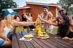 Group of young cheerful friends having fun at picnic outdoors Stock Photography