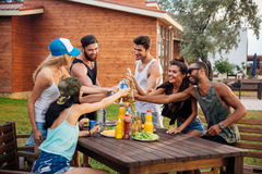 Group of young cheerful friends having fun at picnic outdoors Stock Photos