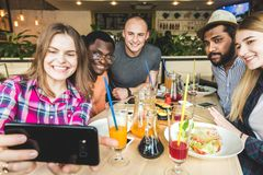 Group of young cheerful friends are sitting in a cafe, eating, drinking drinks. Friends take selfies and take pictures. royalty free stock image
