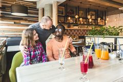 A group of young cheerful friends are sitting in a cafe, eating, drinking drinks, take selfies and take pictures stock photos