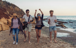 Group of young and cheerful friends walking on beach. One men is playing guitar. Dancing and singing on wild beach stock images