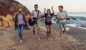 Group of young and cheerful friends walking on beach stock photo