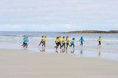 Group of young children running out to sea for surfing lesson Royalty Free Stock Photos