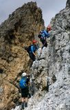Group of young climbers on a steep vertical Via Ferrata. Young climbers in a group on a steep and vertical Via Ferrata in the South Tyrol in the Italian Stock Images