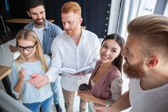Group of young colleagues dressed casual standing together in modern office and brainstorming. stock photo