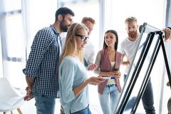 Group of young colleagues dressed casual standing together in modern office and brainstorming. stock photography