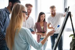 Group of young colleagues dressed casual standing together in modern office and brainstorming. royalty free stock photography