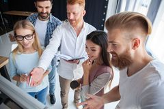 Group of young colleagues dressed casual standing together in modern office and brainstorming. stock image