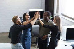 Group of young colleagues giving each other a high five. While standing in an office Royalty Free Stock Photo