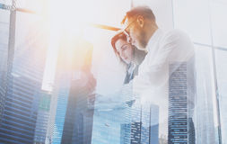 Group of young coworkers on business meeting.Business team in working process.Double exposure,skyscraper building. Blurred background.Flares effect Royalty Free Stock Photo
