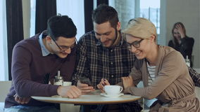 Group of young creative people wearing business casual clothes collaborating at meeting table and discussing work, using stock footage