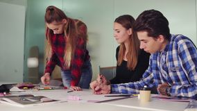 Group of young creative people working together in modern office. Young professionals making sketches sitting at the stock footage