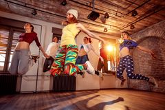 Group of young dancer people jumping during music. Sport, dancing and urban culture concept. Group of dancer people jumping during music. Sport, dancing and royalty free stock image