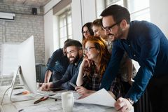 Group of young designers working as team. In office Stock Image