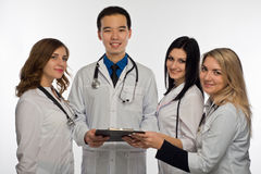 A group of young doctors is discussing something before treatmen. Young doctors are reading documents attached to black clipboard Royalty Free Stock Photo