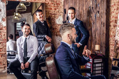Group of young elegant positive mens pose in interior of barbershop. royalty free stock photography