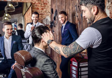Group of young elegant positive mens pose in interior of barbershop. royalty free stock photos