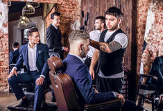 Group of young elegant positive mens pose in interior of barbershop. royalty free stock image