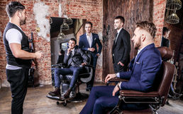 Group of young elegant positive mens pose in interior of barbershop. stock image