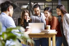 Group of young business people meeting in office. Group of young entrepreneurs asian and caucasian men and women meeting in office discussing business using Royalty Free Stock Photography