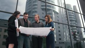 Group of young entrepreneurs with blueprints in hand. designers and architects are holding an outline and talking stock footage