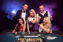 Group of a young wealthy friends are playing poker at a casino. royalty free stock images