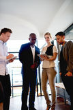 Group of young executives gathered at work. Group of young executives at work consulting and looking at tablet stock photography