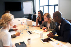 Group of young executives having a work meeting. Group of young executives holding a meeting in a conference room stock images