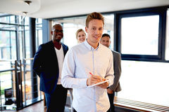 Group of young executives at work smiling and facing camera Royalty Free Stock Photos