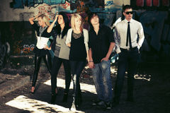 Group of young fashion people against graffiti wall Royalty Free Stock Photo