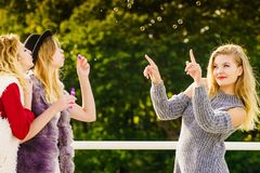Women blowing soap bubbles, having fun royalty free stock photo