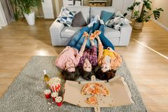 Group of young female friends eating pizza. Three girls eating pizza while lying on the floor with legs on gray sofa stock photo
