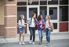 Teen girls leaving school talking and walking together Stock Photos