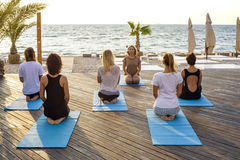 Group of young females practicing yoga on the seaside during the sunrise Stock Images