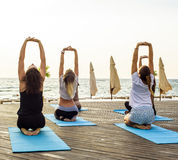 Group of young females practicing yoga on the seaside during the sunrise Royalty Free Stock Photography