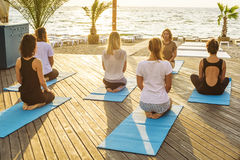 Group of young females practicing yoga on the seaside during the sunrise Royalty Free Stock Photo