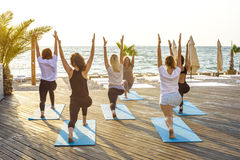Group of young females practicing yoga on the seaside during the sunrise Stock Photography