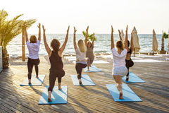 Group of young females practicing yoga on the seaside during the sunrise Stock Photo