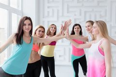 Group of fit women joining hands after having dance fitness class royalty free stock photos