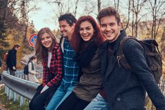 Group of young friends with backpacks sitting on guardrail near road with a beautiful forest and river in the background. Travel, hike, concept royalty free stock images