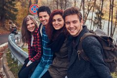 Group of young friends with backpacks sitting on guardrail near road with a beautiful forest and river in the background. Travel, hike, concept royalty free stock photo
