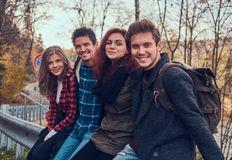 Group of young friends with backpacks sitting on guardrail near road with a beautiful forest and river in the background. Travel, hike, concept stock photo
