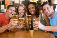 Group of young friends in bar toasting the camera royalty free stock photo