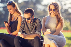 Group of young friends chatting by phones Stock Photography
