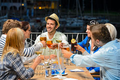 Young friends clinking glasses night restaurant Stock Photography