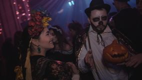 Group of young friends in costumes dancing at night club halloween party