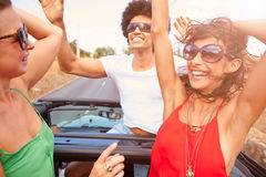 Group Of Young Friends Dancing In Back Of Open Top Car Royalty Free Stock Photography