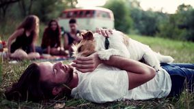 A group of young friends with a dog sitting on grass on a roadtrip through countryside. A group of young friends with a dog sitting on grass by a retro minivan stock video footage